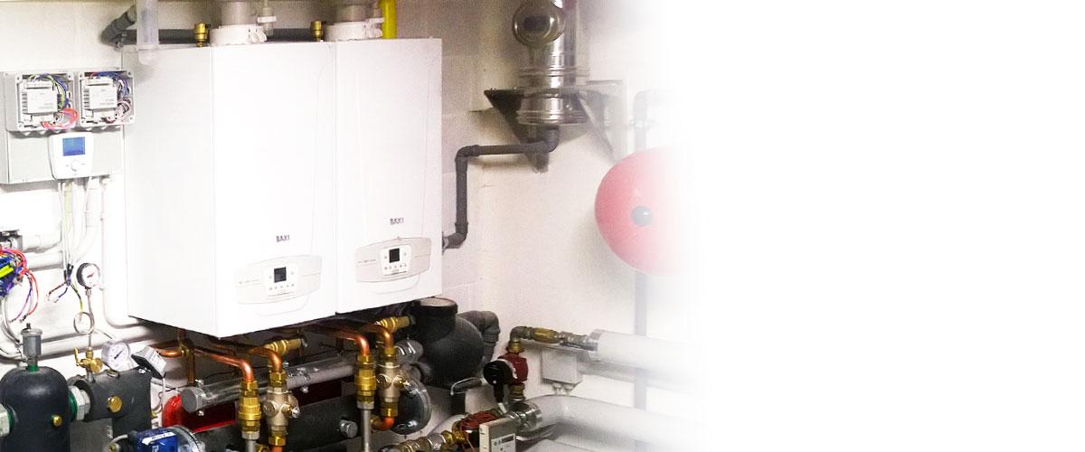 dos calderas de condensacion instaladas en la pared de un cuarto de calderas